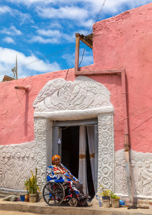 Disabled woman in front of a traditional house in the old town, Harari region, Harar, Ethiopia