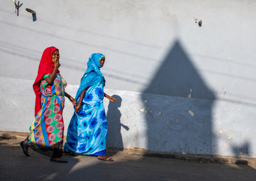 Ethiopian women passing in front of the shadow of a mosque minaret in the street, Harari region, Harar, Ethiopia