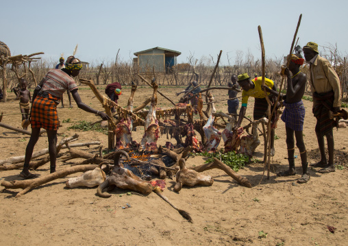Tribe people cooking a cowduring the proud ox ceremony in the Dassanech tribe, Omo valley, Omorate, Ethiopia
