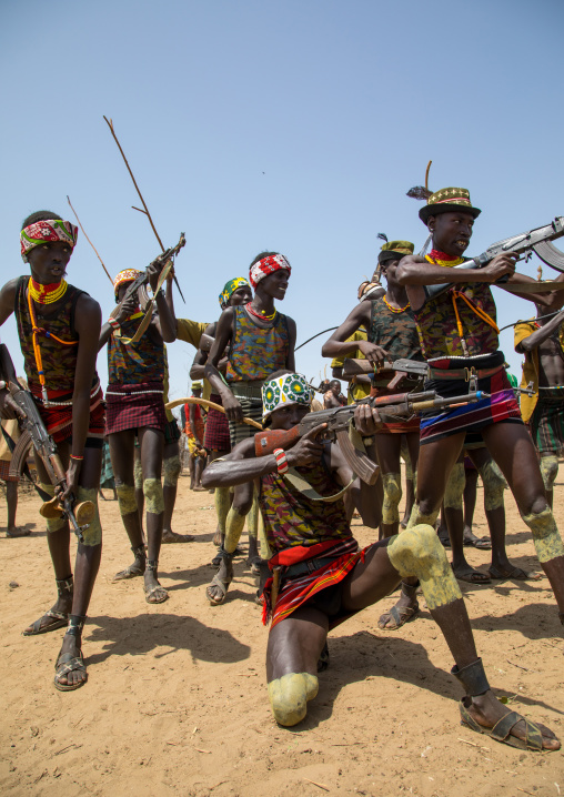 Men shooting with kalashnikovs during the proud ox ceremony in the Dassanech tribe, Turkana County, Omorate, Ethiopia