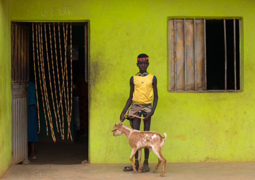 Bana tribe boy with his goat in front of a bar, Omo valley, Key Afer, Ethiopia