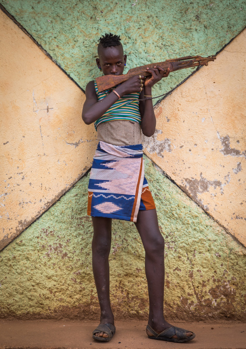 Hamer tribe boy with a wooden kalshnikov, Omo valley, Dimeka, Ethiopia
