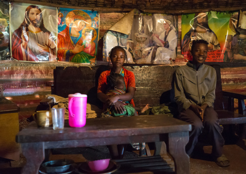 Family sit in a house decorated with christian posters, Gamo Gofa Zone, Ganta, Ethiopia