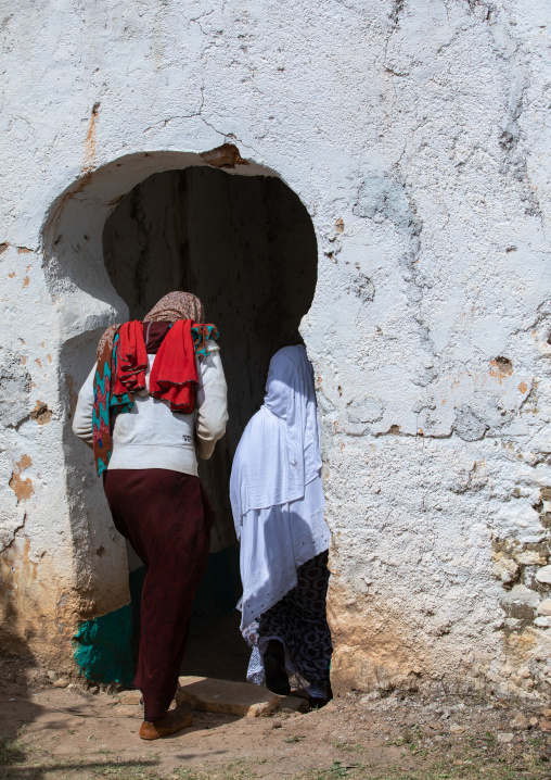 Harari women entering a door in a muslim holy site, Harari Region, Harar, Ethiopia