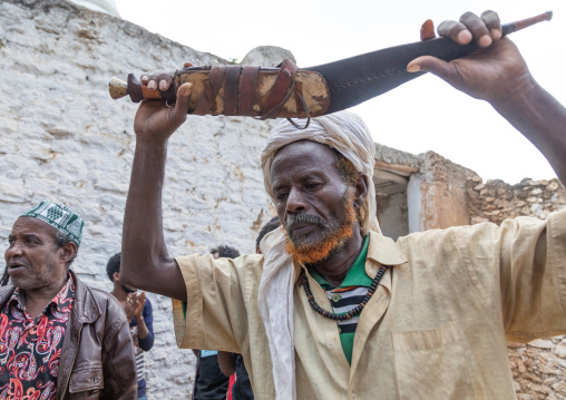 Harari man dancing with a huge knife during a sufi celebration, Harari Region, Harar, Ethiopia