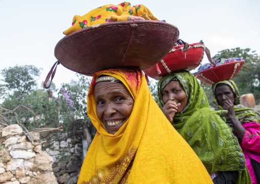 Harari women bringing injeras in baskets on their heads for a muslim celebration, Harari Region, Harar, Ethiopia