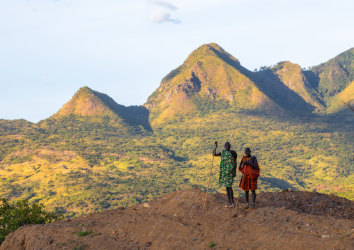 Suri tribe couple in front of a mountain landscape, Omo valley, Kibish, Ethiopia