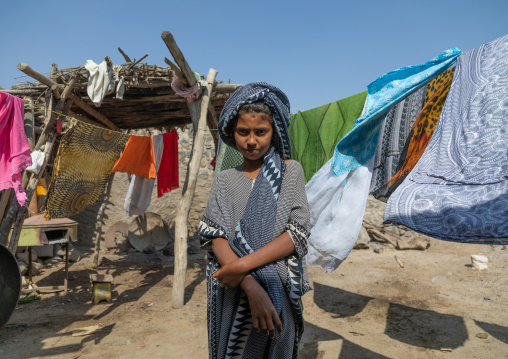 Ethiopian girl in the middle of clothes drying outside, Afar Region, Assayta, Ethiopia