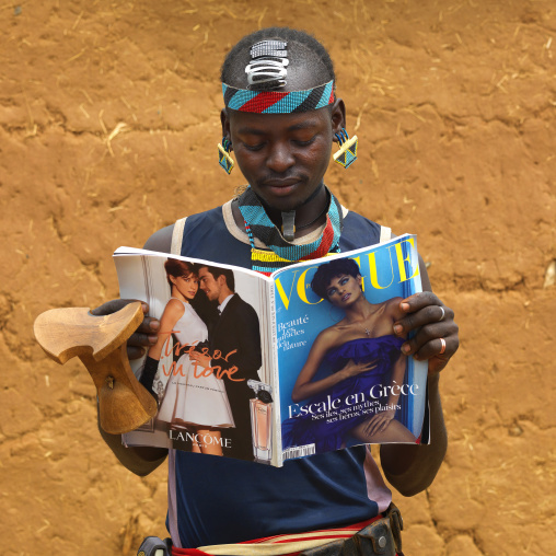 Young fashionable banna tribe man with headrest watching vogue  magazine, Omo valley, Ethiopia