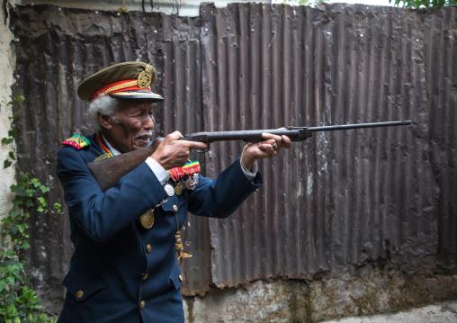 Ethiopian veteran from the italo-ethiopian war in army uniform pretending to shoot, Addis Ababa Region, Addis Ababa, Ethiopia
