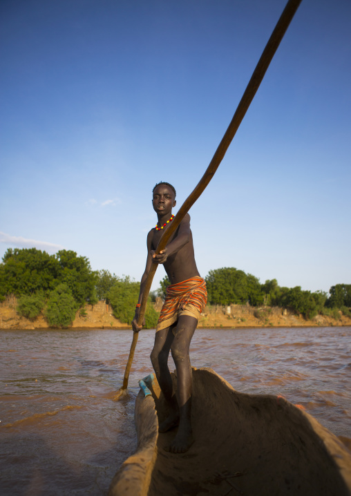 Young Boy Pushing A Boat On The Omo River, Omorate, Omo Valley, Ethiopia