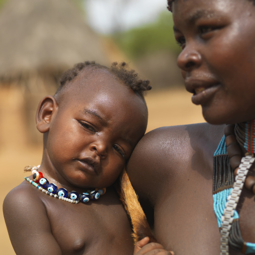 Tsemay mother and her baby in arms both with beaded necklaces, Omo valley, Ethiopia