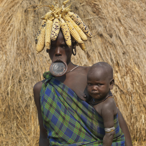 Mother Mursi Woman Wearing Corn Cob Headdress And Clay Plate Carrying Baby Ethiopia