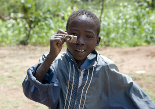 Portrait Of A Konso Tribe Boy Pretending To Take A Picture With A Fake Wooden Camera, Konso, Omo Valley, Ethiopia