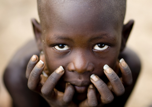 Close-up Portrait Of A Karo Tribe Boy Holding His Head In His Hands, Korcho Village, Omo Valley, Ethiopia
