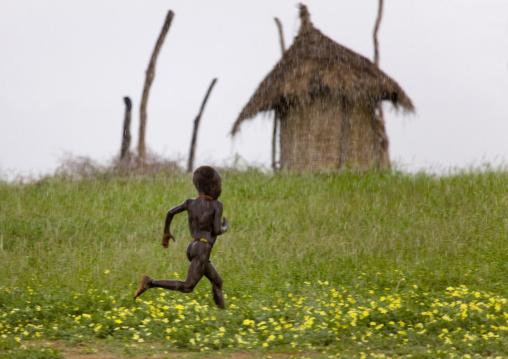 Kid From Karo Tribe Running Under The Rain, Korcho Village, Omo Valley, Ethiopia