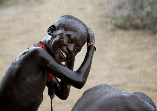 Kids From Karo Tribe Having A Shower Under The Rain, Korcho Village, Omo Valley, Ethiopia