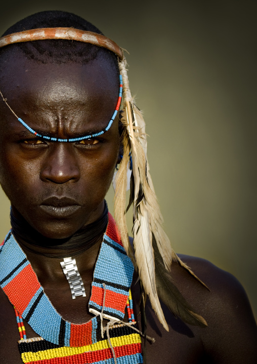 Portrait of a young tsamay whipper with feathers attached to his hairband and traditional necklace, Turmi, Ethiopia