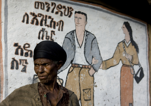 Couple painted on a wall with a senior black woman standing near, Addis ababa, Ethiopia