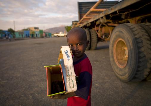 Boy collecting boxes in the street, Assaita, Ethiopia