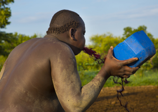 Bodi Tribe Man Spilling Out Cow Blood For New Year Kael Ceremony, Hana Mursi, Omo Valley, Ethiopia