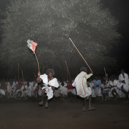 Night Shot Of Two Karrayyu Tribe Men During A Choreographed Stick Fighting Dance At Gadaaa Ceremony, Metahara, Ethiopia