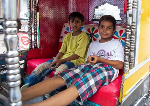 Two indian boys sit in a rickshaw, Rajasthan, Jodhpur, India