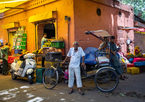 Indian man with his rickshaw in a vegetables and fruits market, Rajasthan, Jaipur, India