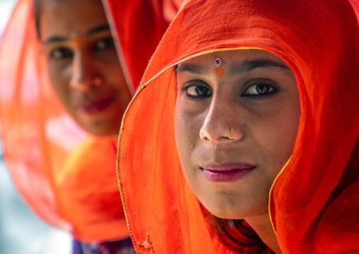 Portrait of rajasthani women in orange saris, Rajasthan, Jaisalmer, India
