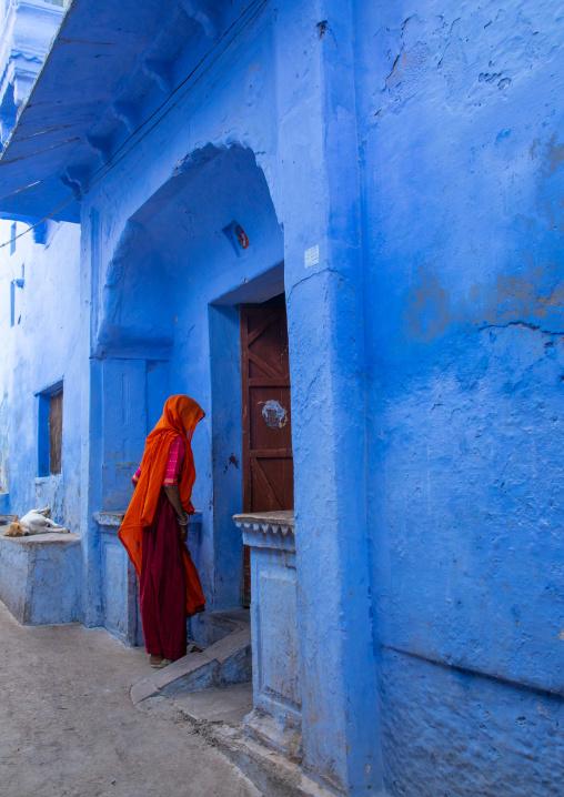 Indian woman entering an old blue house of a brahmin, Rajasthan, Bundi, India