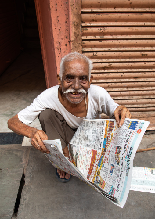 Smiling indian man reading the newspaper in the street, Rajasthan, Jaipur, India