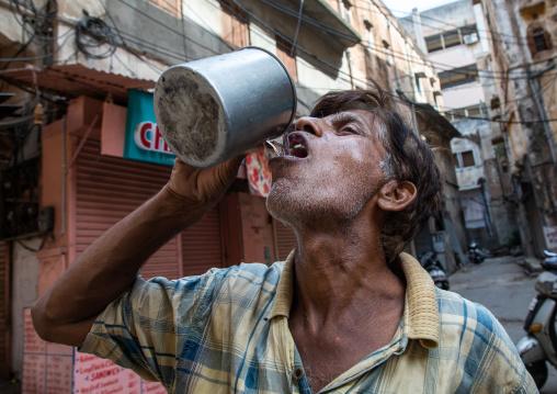 Indian man drinking in the street, Rajasthan, Jaipur, India