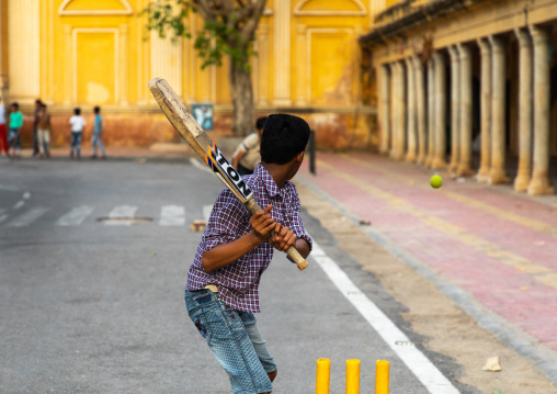 Young boy holding a cricket bat and playing in the street, Rajasthan, Jaipur, India