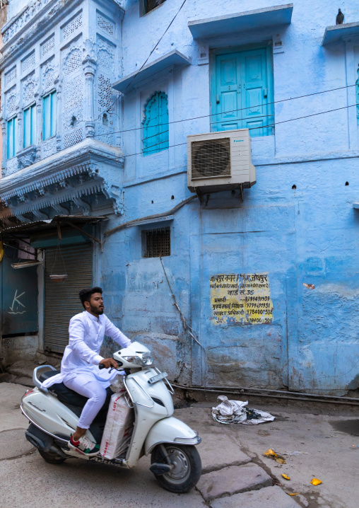 Indian man passing by an old blue house of a brahmin in scooter, Rajasthan, Jodhpur, India