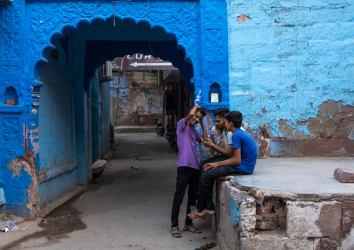 Indian young men sit at the entrance of an old blue house of a brahmin, Rajasthan, Jodhpur, India