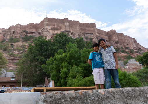 Children on the rooftop of their house in front of the fort, Rajasthan, Jodhpur, India