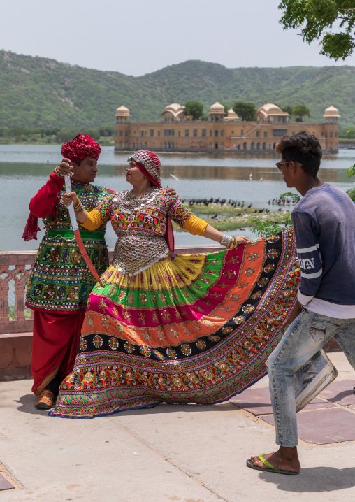 Indian tourists posing in traditional clothing in front of jal mahal, Rajasthan, Jaipur, India