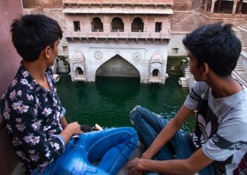 Indian boys looking at toorji ka Jhalra stepwell, Rajasthan, Jodhpur, India