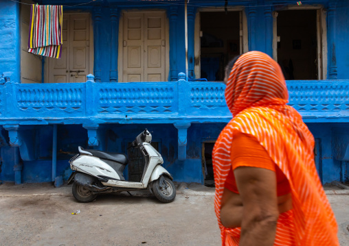 Indian woman in front of an old blue house of a brahmin, Rajasthan, Jodhpur, India