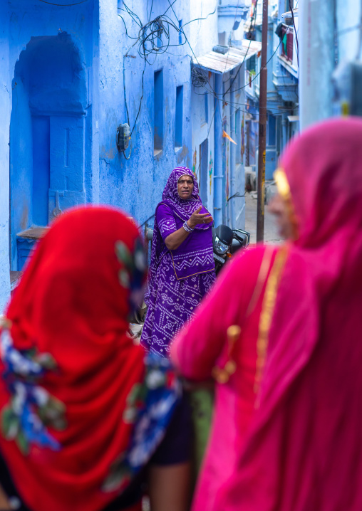 Rajasthani women in front of old blue houses, Rajasthan, Bundi, India