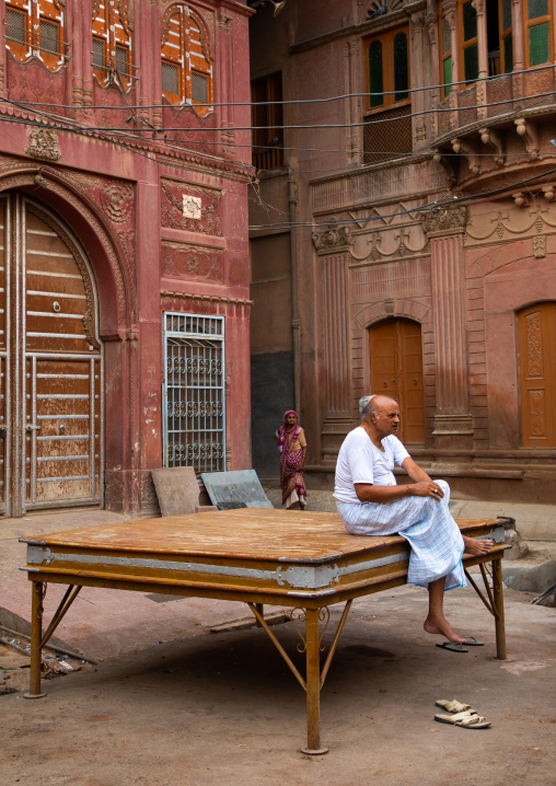 Indian man sit on a resting bed in front of a beautiful haveli in the old city, Rajasthan, Bikaner, India
