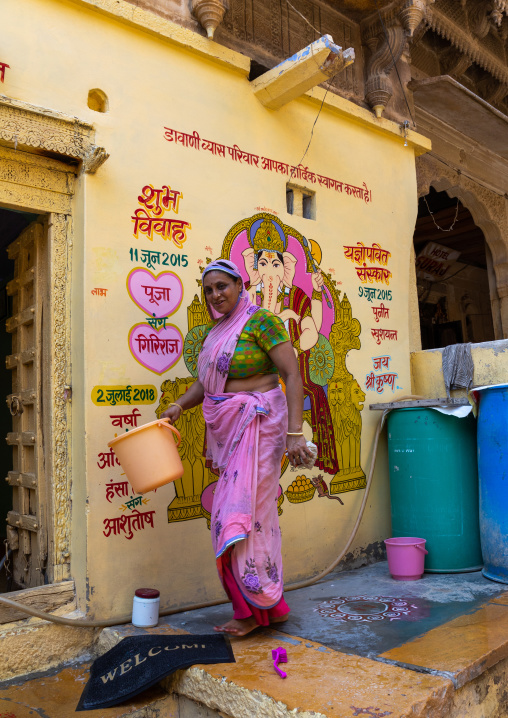 Portrait of a rajasthani woman in traditional sari washing her home, Rajasthan, Jaisalmer, India