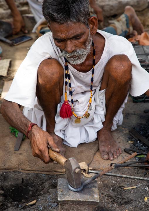 Indian blacksmith forging metal at work, Rajasthan, Jaisalmer, India