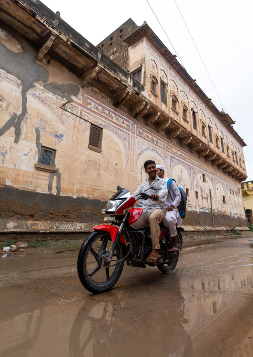 Indian people riding a motorbike and passing by an old historic haveli, Rajasthan, Nawalgarh, India