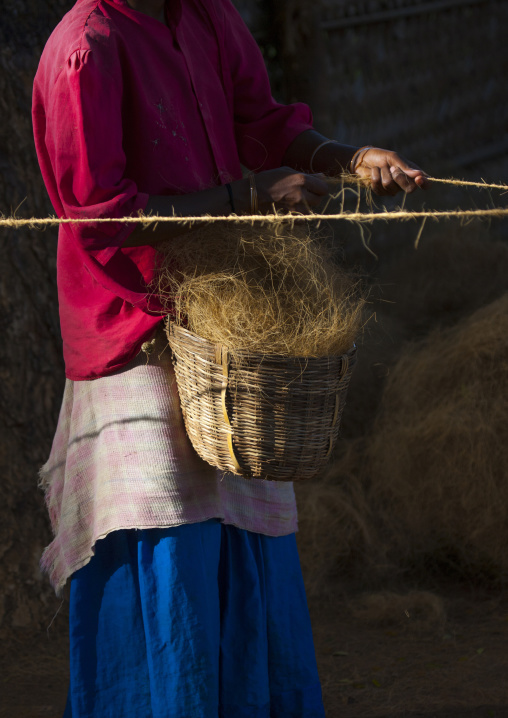 Woman Holding A Basket Full Of Hemps And Making Ropes In A Village Near Madurai, India