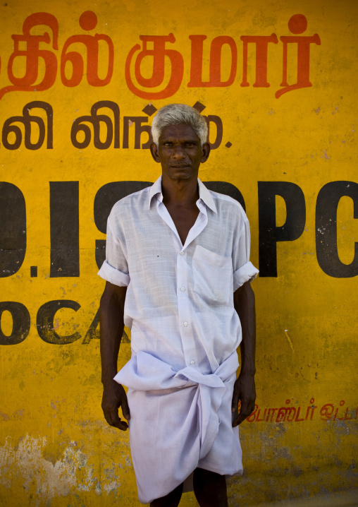 Indian Man With Gray Hairs And A White Shirt Posing In Front Of A Yellow Wall, Periyar, India