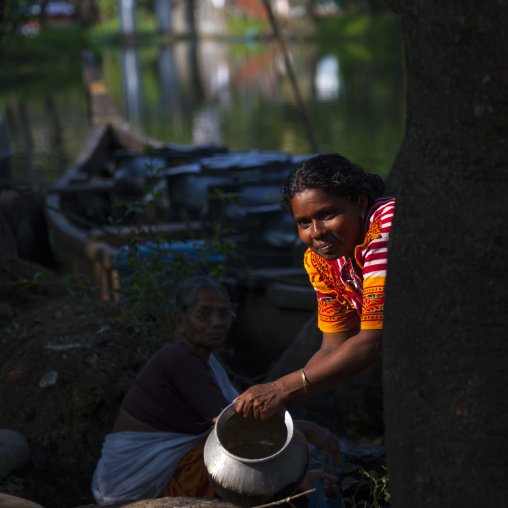 Two Women In Front Of A Rowboat And By The Waterside, Alleppey, India