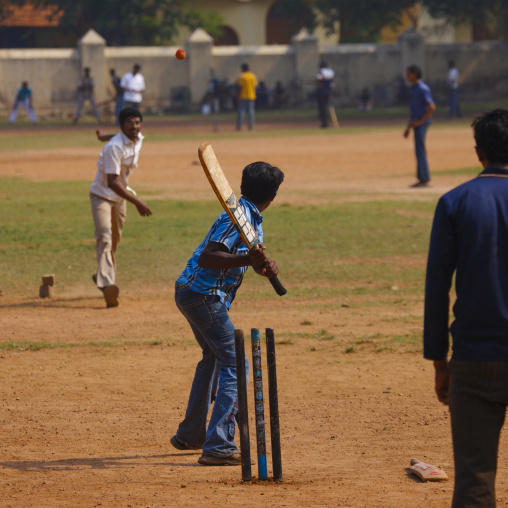 Group Of Young Men Practicing Cricket On A Public Ground, Kochi, India