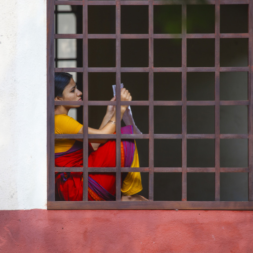 Young Woman Holding A Sheet Of Paper Sitting On The Edge Of A Bar Window At Dakshinachitra Dance Center, Chennai, India