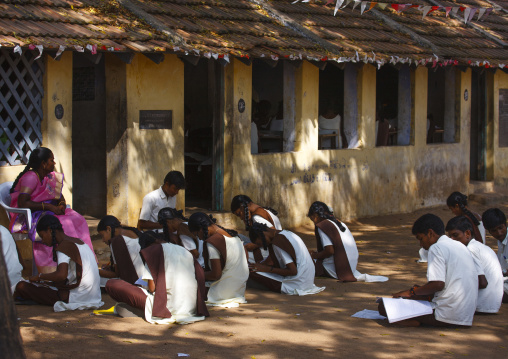 Group Of Students In Uniform Studying Sitting On The Ground In Front Of The Classroom, Mahabalipuram, India